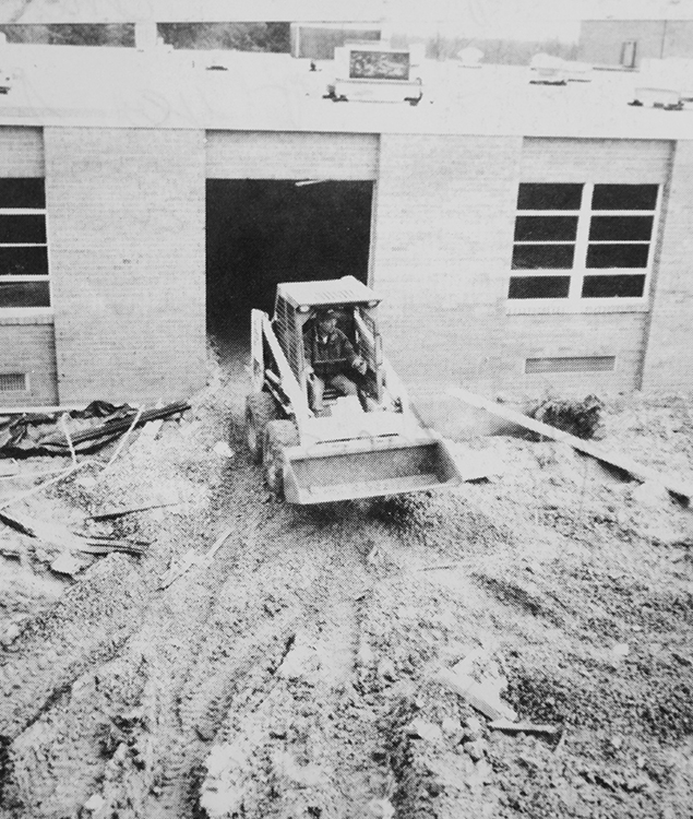 Black and white photograph of a construction worker operating a Bobcat next to the building.